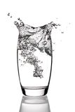 Glass of water. Water splashing into glass, isolated on a white background royalty free stock photo