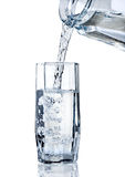Glass of water. Fresh water being poured into a glass isolated on white Royalty Free Stock Images