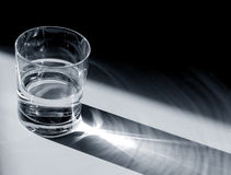Glass of Water. Small glass of water in the sunlight by the shadows royalty free stock photos