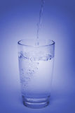 Glass with water. The stream of water flowing in a glass with water Royalty Free Stock Image