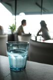 Glass of water. Blue glass filled with fresh water on a table into a restaurant Stock Images