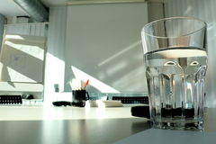 Glass of water. A glass of water in the foreground in a meeting room royalty free stock images