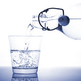 A glass of water. Being poured from a bottle Royalty Free Stock Photos