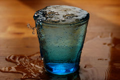 Glass of water. Overflowing on the table Stock Photo