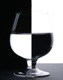 A glass with water. In backlight on the black and white contras Royalty Free Stock Photography