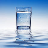 Glass of water. A glass of water with drops and reflection royalty free stock photos