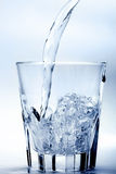 Glass of water. Fresh water flowing in a glass in silver tonality Royalty Free Stock Image