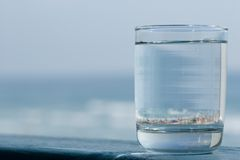 Glass on the Water. Glass of Water with Beach Reflection inside Stock Image