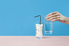 Glass of water against sugar, diabetes disease, sweet addiction, hand take a glass. Blue table Stock Image