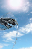 Glass of water against a sunny sky. A glass of water being poured against a bright sunny cloudy blue sky background Stock Photos
