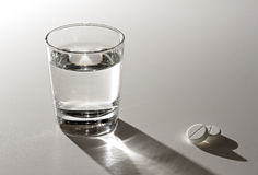 Glass of water and aspirin. On a white table Stock Images