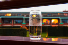 Glass of water on the balcony with evening lights background. Glass of water on the edge of a balcony of a hotel room, on the background blurred lights at dusk Stock Images