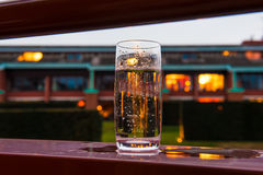 Glass of water on the balcony with evening lights background. Glass of water on the edge of a balcony of a hotel room, on the background blurred lights at dusk Stock Photos