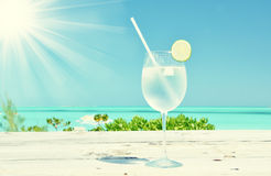 Glass of water on the beach Royalty Free Stock Image