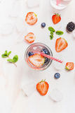 Glass with water ,berries, ice cubes, red straw and ingredients on white wooden background Stock Photo