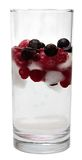 Glass of water with berries and ice. Raspberries, blueberries, cranberries, currants. Isolated white background. Glass of water with berries and ice Stock Image