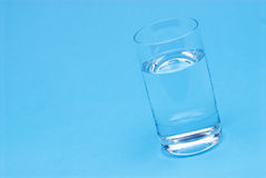 Glass of water on blue Royalty Free Stock Photos