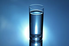 Glass with water on blue Stock Images