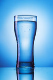 Glass of water on blue background Royalty Free Stock Photos