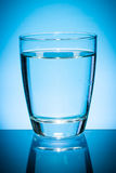 Glass of water  on blue. Royalty Free Stock Photos