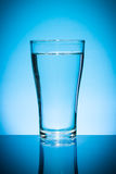 Glass of water  on blue. Royalty Free Stock Image