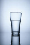 Glass of water on blue background. Object Stock Photography
