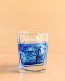 Glass of water with blue liquid Stock Photos