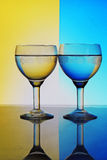 Glass of water on blue yellow background Stock Images