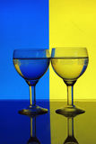 Glass of water on blue yellow background Royalty Free Stock Images