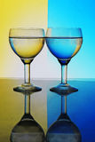Glass of water on blue yellow background Royalty Free Stock Photos