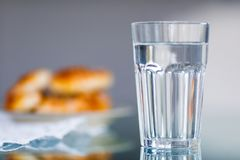 A glass of water and blurred cakes. In the background stock image