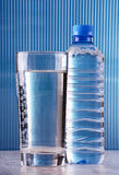 Glass of water and bottle on blue background Stock Image