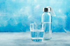 Glass of water with a bottle. On table on blue background stock photography