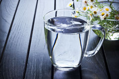 Glass Of Water. With a bowl of flowers Stock Photo