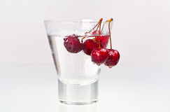 Glass with water and cherries Stock Image