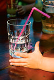 A glass of water and a children's hand. A glass of water with a straw is on the table and extends a hand to him a child Royalty Free Stock Image
