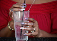 Glass of water. Close up of African American women`s hands with beautiful manicure holding  glass with ice water Stock Photo
