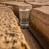 A Glass Of Water In Crack Parched Soil II. A glass of water on a parched soil during drought and dry season Stock Photos