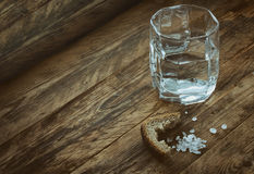 Glass of water, crust of black bread, salt. On old wooden table,  concept of hunger need Stock Photo