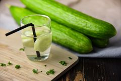 Glass of water with cucumber on wooden table. Fresh Stock Photo