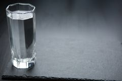 A glass with water in dark background royalty free stock photos