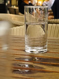 Glass with water and Drop on table. Glass with water and Drop on Wooden tables Stock Image