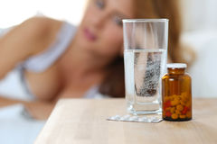 Glass of water and drugs standing on bedside table Stock Image