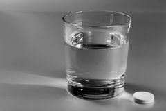 Glass of water and an effervescent pill Royalty Free Stock Photos