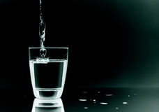 Glass of water. Filling in glass with water on black background royalty free stock photo
