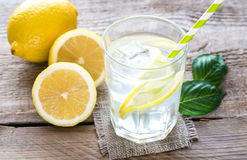Glass of water with fresh lemon juice. On the wooden table stock photo