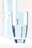 Glass of water in front of water bottle isolated on white.  stock image