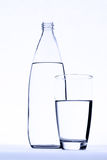 Glass of water in front of water bottle isolated on white.  royalty free stock photos