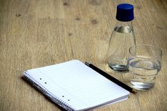 Glass of water, glass bottle, notebook and pencil on the table royalty free stock photos