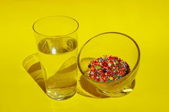 Glass Of Water And Glass Of Colorful Candies Over Yellow Background. Food, Diet, Choice Concept. Abstract Colorful Food Background stock images